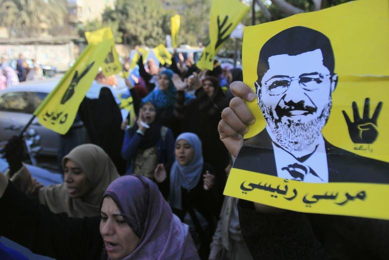 Supporters of the Muslim Brotherhood and ousted Egyptian President Mohamed Mursi shout slogans against the military and interior ministry while holding his poster and gesturing with four fingers in front of Al Rayyan mosque after Friday prayers in the southern suburb of Maadi, on the outskirts of Cairo in this December 27, 2013 file photo. REUTERS/Amr Abdallah Dalsh/Files