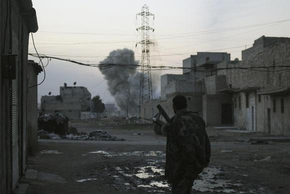 Smoke rises while a Free Syrian Army fighter stands at the Karm al-Tarab neighborhood frontline in Aleppo February 1, 2014. REUTERS/Ammar Abdullah