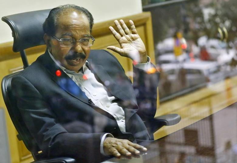 India's Oil Minister M. Veerappa Moily, is pictured through a glass as he speaks during an interview with Reuters in New Delhi January 23, 2014. REUTERS/Anindito Mukherjee