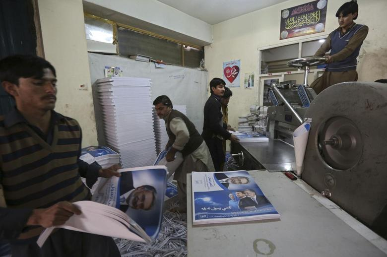 Labourers print posters of presidential election candidates at a printing press in Kabul, January 29, 2014. REUTERS/Omar Sobhani
