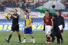 Jogadores e técnicos do Parma e Roma inspecionam campo em partida cancelada pela forte chuva, em Roma. 02/02/2014 REUTERS/Giampiero Sposito