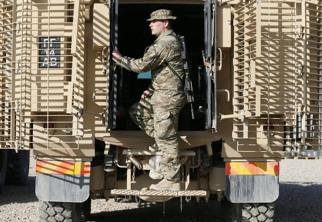 A British soldier works on a vehicle which will be re-deployed to the UK at Camp Bastion, outside Lashkar Gah, in Helmand Province, Afghanistan December 20, 2012. REUTERS/Stefan Wermuth