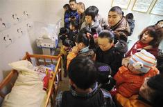 Residents visit an abandoned baby (L) lying in a crib at a baby hatch in Guiyang, Guizhou province January 12, 2014. REUTERS/Stringer