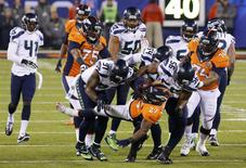 Denver Broncos Knowshon Moreno (C) is tackled by Seattle Seahawks Chris Clemons (91) in the first quarter during the NFL Super Bowl XLVIII football game in East Rutherford, New Jersey, February 2, 2014. REUTERS/Eduardo Munoz
