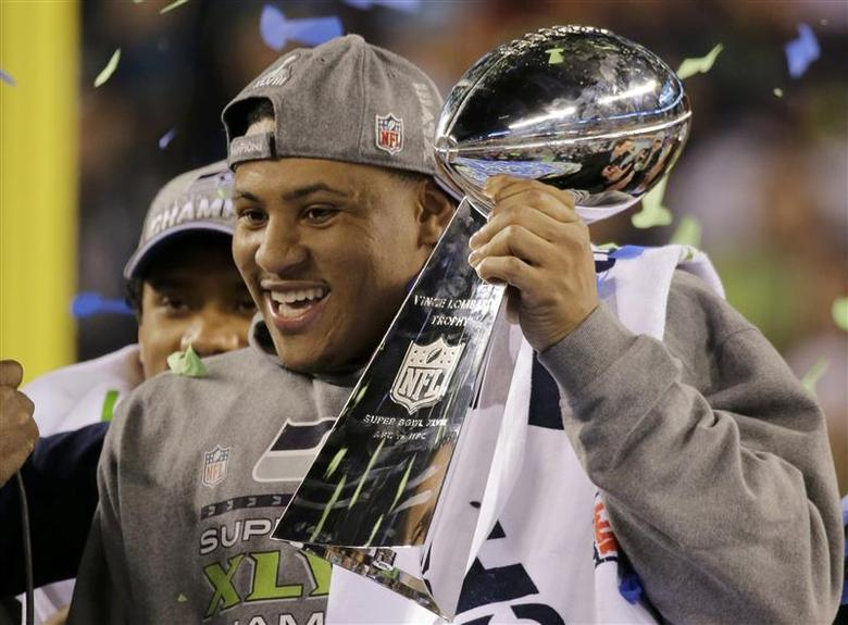 Seattle Seahawks outside linebacker Malcolm Smith celebrates with the Vince Lombardi trophy after defeating the Denver Broncos in the NFL Super Bowl XLVIII football game in East Rutherford, New Jersey, February 2, 2014. REUTERS/Ray Stubblebine