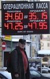 Мужчина стоит у пункта обмена валют в Москве 29 января 2014 года. Рубль в небольшом минусе к бивалютной корзине и её компонентам утром понедельника, факторами давления остаются глобальный спрос на американскую валюту в ущерб высокорискованным инструментам, шаги ЦБР к свободному плаванию рубля, риски замедления экономики РФ. REUTERS/Sergei Karpukhin