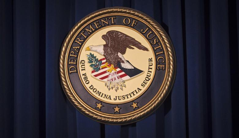 The Department of Justice (DOJ) logo is pictured on a wall after a news conference to discuss alleged fraud by Russian Diplomats in New York December 5, 2013. REUTERS/Carlo Allegri