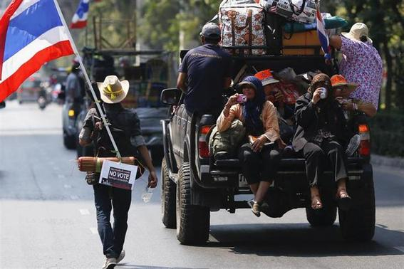 An anti-government protester carrying a national flag, a guitar and a 'No Vote' sign follows others moving from one protest camp to another in Bangkok February 3, 2014. REUTERS/Damir Sagolj