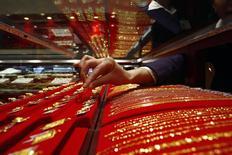 Продавец убирает с витрины ювелирного магазина в Суйнине золотое украшение 29 марта 2010 года. Цены на золото малоподвижны после первого за шесть недель снижения на фоне укрепления доллара США и отсутствия китайских покупателей. REUTERS/Stringer