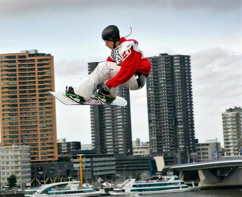 Norway's Torstein Horgmo leaps in the air with the skyline of Rotterdam as a backdrop during the Snowboard FIS World Cup 2006 Big-Air Competition in Rotterdam, the Netherlands, October 9, 2005. REUTERS/Michael Kooren