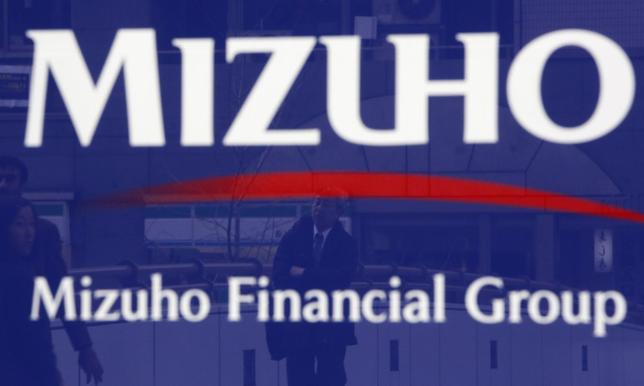 A man is reflected on an advertisement board of Mizuho Financial Group's Mizuho Bank in Tokyo January 30, 2014. REUTERS/Yuya Shino