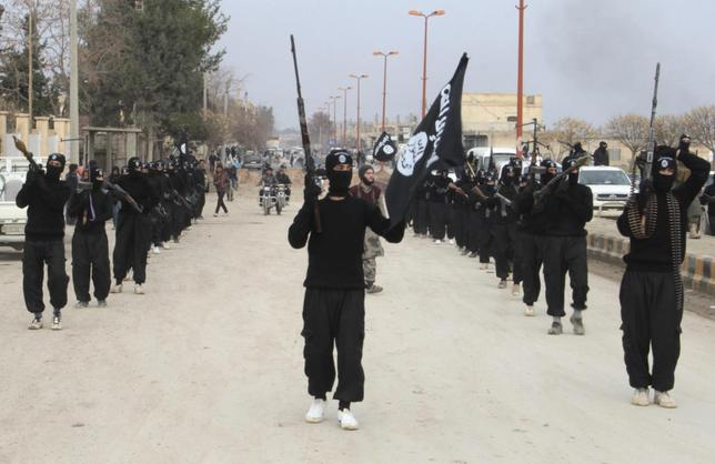 Fighters of al-Qaeda linked Islamic State of Iraq and the Levant carry their weapons during a parade at the Syrian town of Tel Abyad, near the border with Turkey January 2, 2014. REUTERS/Yaser Al-Khodor