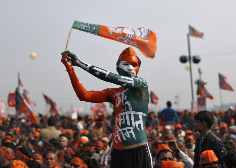 A supporter of India's main opposition Bharatiya Janata Party (BJP) waves the party's flag during a rally being addressed by Gujarat's Chief Minister and Hindu nationalist Narendra Modi, the prime ministerial candidate for BJP, ahead of the 2014 general elections, at Meerut in the northern Indian state of Uttar Pradesh February 2, 2014. REUTERS/Ahmad Masood