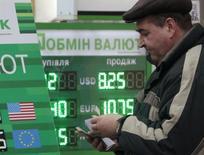Мужчина пересчитывает деньги около обменного пункта в Киеве 14 ноября 2012 года. Котировки гривны на межбанковском рынке Украины, в столице которой две недели продолжается противостояние протестующих с милицией, пробили в понедельник уровень 8,7 за $1, потеряв еще почти 10 копеек по сравнению с пятницей. REUTERS/Anatolii Stepanov