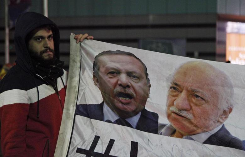 A demonstrator hold pictures of Turkey's Prime Minister Tayyip Erdogan and Turkish cleric Fethullah Gulen (R), during a protest against Turkey's ruling AK Party (AKP), demanding the resignation of Erdogan, in Istanbul December 30, 2013. REUTERS/Osman Orsal