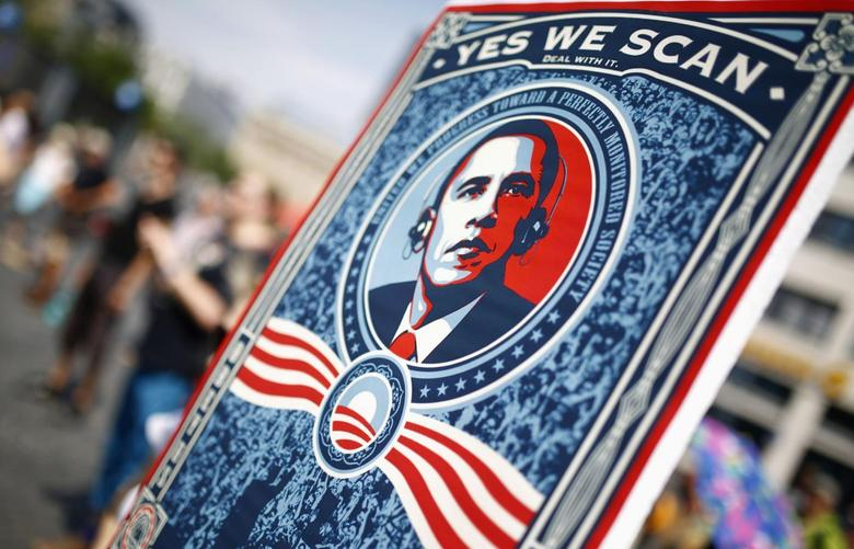 A protester holds a placard showing U.S. President Barack Obama with the phrase ''Yes we scan'' during a demonstration against the National Security Agency (NSA) and in support of U.S. whistleblower Edward Snowden in Frankfurt, July 27, 2013. REUTERS/ Kai Pfaffenbach