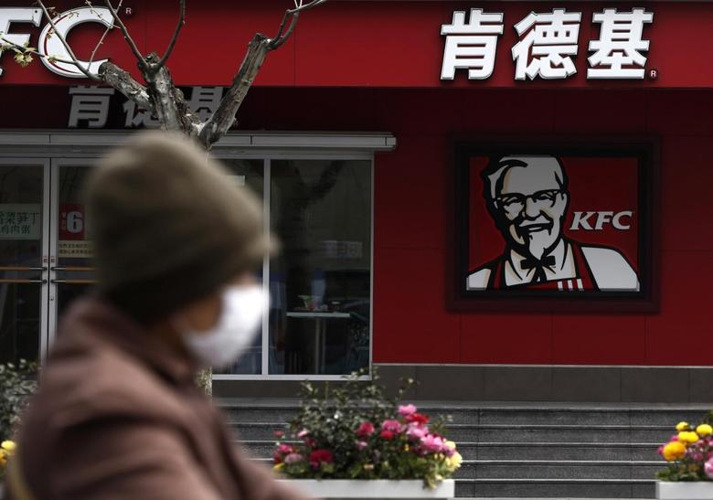 A woman, wearing a mask, rides past a KFC restaurant in Shanghai April 11, 2013. REUTERS/Aly Song