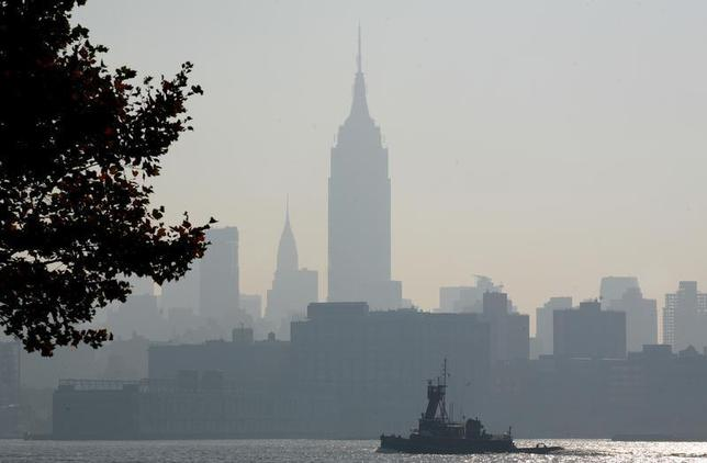 The haze shrouded skyline of New York is a backdrop for a boat moving up the Hudson River in Hoboken, New Jersey August 3, 2006. REUTERS/Gary Hershorn