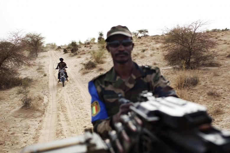 A Malian soldier holds a machine gun mounted on a pick-up truck during a military escort outside Timbuktu July 27, 2013. REUTERS/Joe Penney