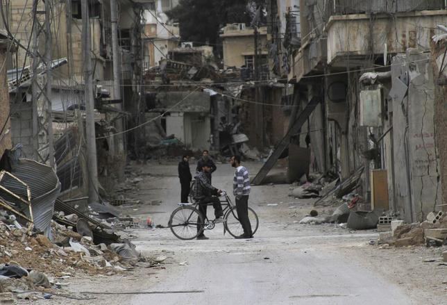 Men chat near buildings damaged by what activists said was shelling by forces loyal to Syria's President Bashar al-Assad in Daraya, near Damascus February 2, 2014. Picture taken February 2, 2014.REUTERS/Omar Abu Bakr