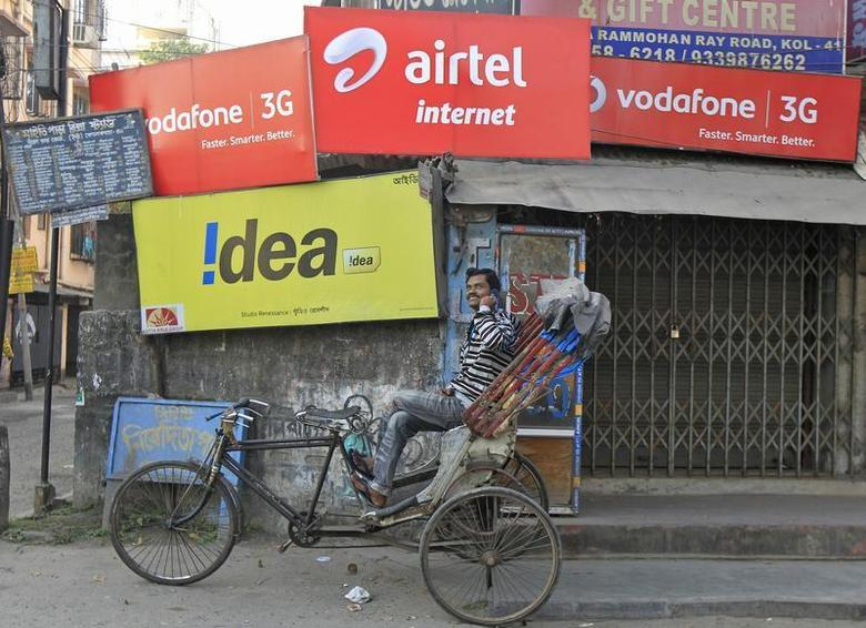 A rickshaw puller speaks on his mobile phone as he waits for customers in front of advertisement billboards belonging to telecom companies in Kolkata February 3, 2014. REUTERS/Rupak De Chowdhuri