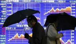 Люди проходят мимо брокерской конторы в Токио 4 февраля 2014 года. Азиатские фондовые рынки значительно снизились во вторник из-за ухудшения макроэкономической статистики США. REUTERS/Yuya Shino