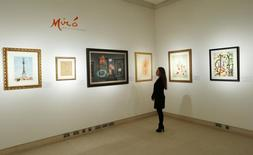 A Christie's employee looks at a selection of artworks by Joan Miro, which will be sold next week, at Christie's auction house in London January 30, 2014. REUTERS/Suzanne Plunkett