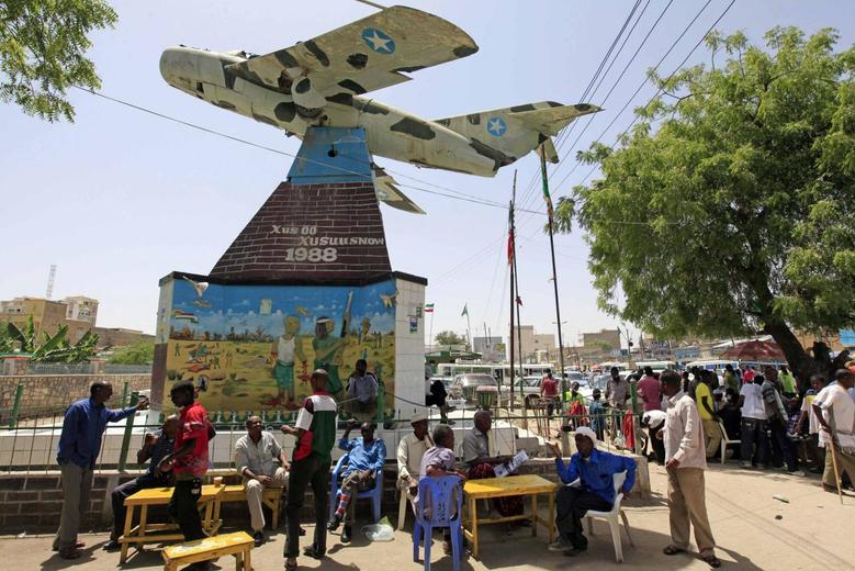 Residents of Somaliland sit under a war memorial of a MiG fighter jet in the centre of town in Hargeisa May 19, 2013. REUTERS/Feisal Omar