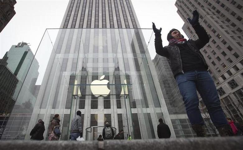 A man poses for a photo in front of the Apple store on 5th Avenue in New York, December 26, 2013. REUTERS/Carlo Allegri/Files