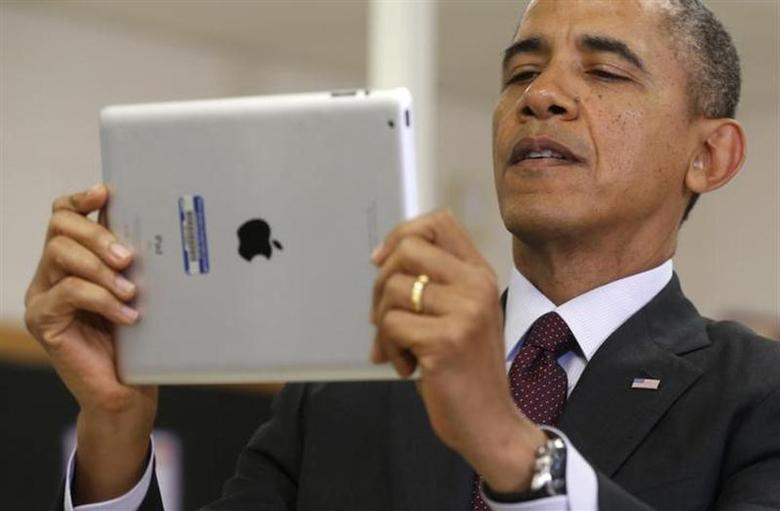 U.S. President Barack Obama holds up an iPad during a visit to Buck Lodge Middle School in Adelphi, Maryland February 4, 2014. REUTERS/Kevin Lamarque