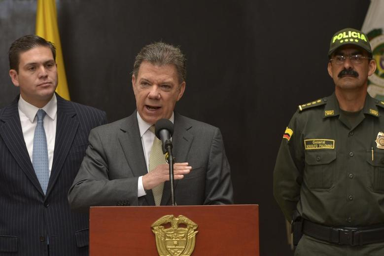 Colombia's President Juan Manuel Santos (C) speaks in between Defense Minister Juan Carlos Pinzon (L) and police chief Rodolfo Palomino during an official ceremony at the police headquarters in Bogota February 4, 2014. REUTERS/Andres Piscov/Colombian Presidency/ Handout via Reuters