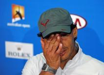 Rafael Nadal of Spain wipes his face at a news conference after losing his men's singles final match against Stanislas Wawrinka of Switzerland at the Australian Open 2014 tennis tournament in Melbourne January 26, 2014. REUTERS/Bobby Yip