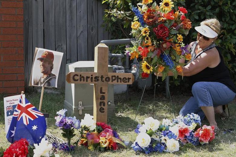 Neighborhood resident Sherrie Shannon of Duncan, Oklahoma, places flowers at a memorial at the scene where Australian college student Christopher Lane, 23, of Melbourne, was found dead of a gunshot wound on Friday in Duncan, Oklahoma August 21, 2013. REUTERS/Bill Waugh