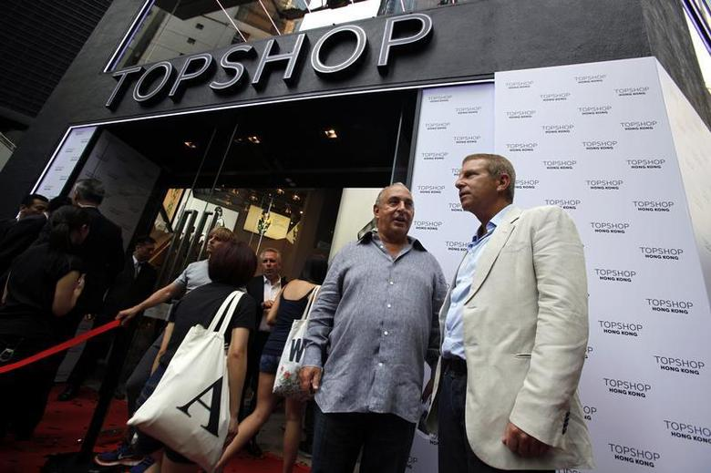 British billionaire and CEO of the Arcadia Group Philip Green (2nd R) chats with Group President and Chief Executive Officer of Li & Fung Ltd Bruce Rockowitz (R) as customers enter the Topshop flagship store during its opening ceremony in Hong Kong June 6, 2013. REUTERS/Bobby Yip