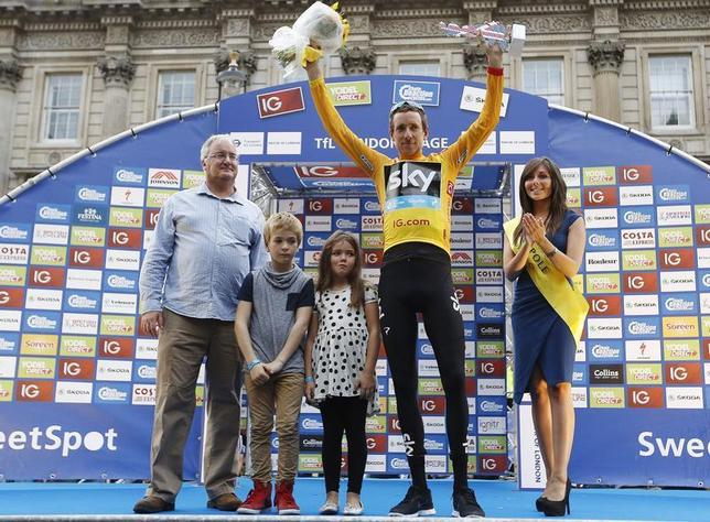 Britain's Bradley Wiggins (2nd R), with his children Ben and Isabella, celebrate being the overall winner of the Tour of Britain and receiving the gold jersey in Whitehall, central London September 22, 2013. REUTERS/Olivia Harris
