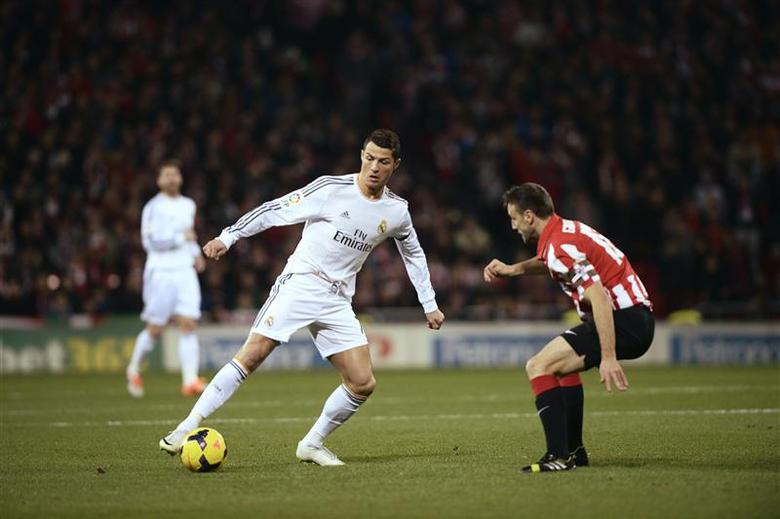 Real Madrid's Cristiano Ronaldo (L) fights for the ball with Athletic Bilbao's Carlos Gurpegi during their Spanish first division soccer match at San Mames stadium in Bilbao February 2, 2014. REUTERS/Vincent West
