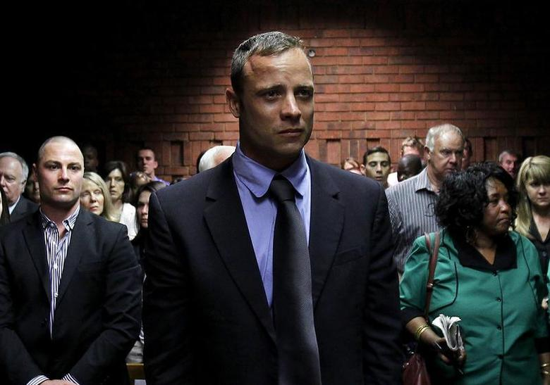 Oscar Pistorius awaits the start of court proceedings while his brother Carl (L) looks on, in the Pretoria Magistrates court February 19, 2013. REUTERS/Siphiwe Sibeko