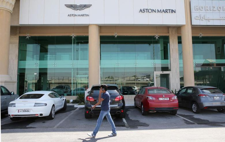 A man walks in front of cars parked outside an Aston Martin showroom in Doha, October 19, 2013. REUTERS/Fadi Al-Assaad (