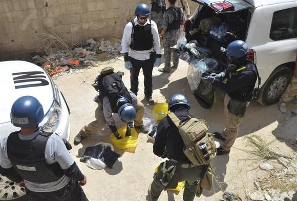 U.N. chemical weapons experts prepare before collecting samples from one of the sites of an alleged chemical weapons attack in Damascus' suburb of Zamalka August 29, 2013. REUTERS/Bassam Khabieh/Files