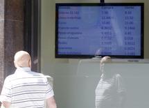 Una persona observa un monitor con precios de monedas en una casa de cambios en Buenos Aires, ene 27 2014. Argentina probablemente no abandonará en el corto plazo los estrictos controles de cambios que mantiene para impedir una fuga de divisas y usaría sus reservas internacionales para evitar otra devaluación abrupta, mostró un sondeo de Reuters. REUTERS/Enrique Marcarian