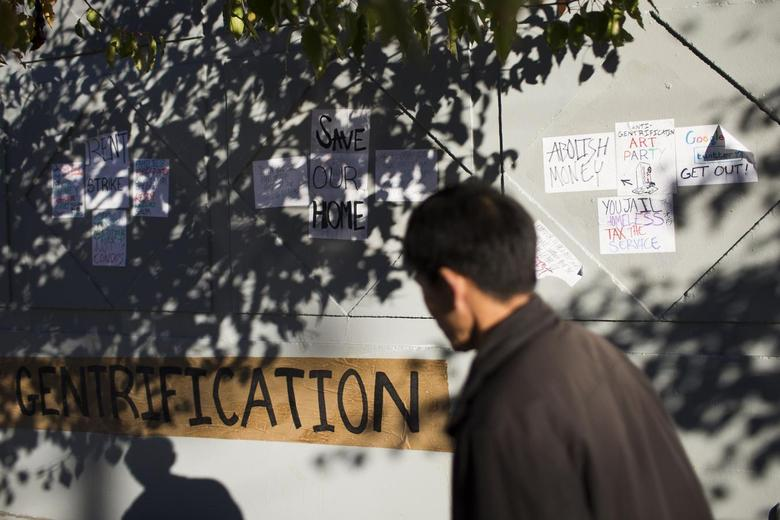 A man walks past a collection of signs opposing the gentrification of Mission District by technology companies in San Francisco, California December 9, 2013. REUTERS/Stephen Lam