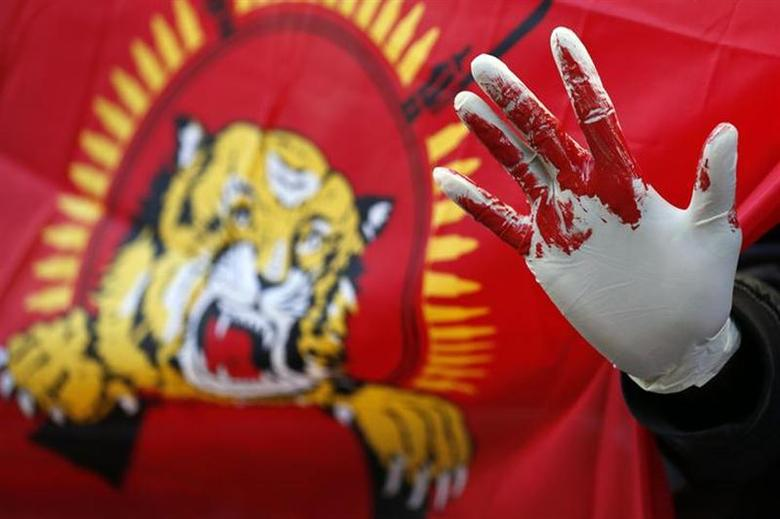 A Tamil demonstrator holds up a hand as they wear a glove covered with fake blood during a protest near the Commonwealth Secretariat in London November 15, 2013. REUTERS/Stefan Wermuth/Files