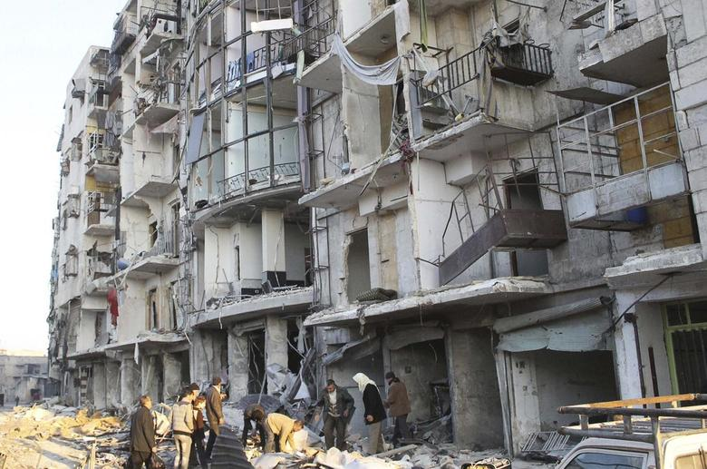 Residents inspect damage after what activists said was a barrel bomb dropped by forces loyal to Syria's President Bashar al-Assad in the Tariq al-Bab neighbourhood of Aleppo February 5, 2014. REUTERS/Hosam Katan
