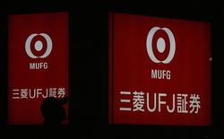 A pedestrian walks past a logo of Mitsubishi UFJ Securities in Tokyo February 3, 2009. REUTERS/Yuriko Nakao