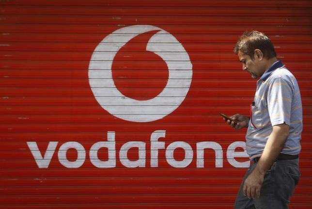 A man checks his mobile phone as he walks past a shop displaying the Vodafone logo on its shutter in Mumbai January 15, 2014. REUTERS/Danish Siddiqui