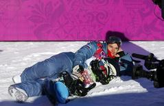 Russia's Alexey Sobolev poses lying in the snow at the finish line during the men's slopestyle snowboarding qualifying session at the 2014 Sochi Olympic Games in Rosa Khutor February 6, 2014 . REUTERS/Mike Blake