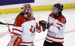 Canada's Shannon Szabados (L) and Gillian Apps celebrate after defeating Russia in their semi-final game at the IIHF Ice Hockey Women's World Championship in Ottawa April 8, 2013 file photo. REUTERS/Chris Wattie