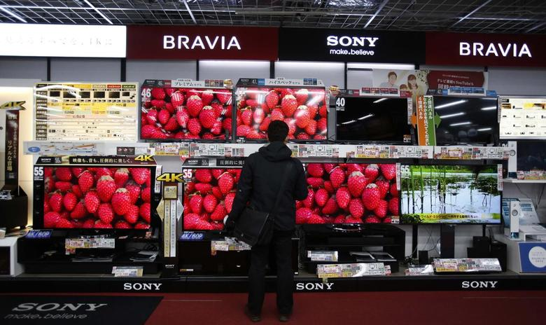 A shopper looks at Sony Corp's Bravia televisions at an electronics retail store in Tokyo February 5, 2014. Japanese electronics maker Sony Corp warned it expects a net loss of 110 billion yen ($1.1 billion) this fiscal year as it absorbs restructuring costs linked to its moves to exit the personal computer business. Picture taken February 5, 2014. REUTERS/Yuya Shino
