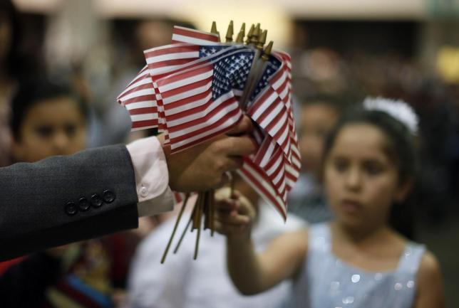 A man hands out U.S. flags at a naturalization ceremony for 3,703 new U.S. citizens from 130 countries, in Los Angeles, California, December 17, 2013. REUTERS/Lucy Nicholson