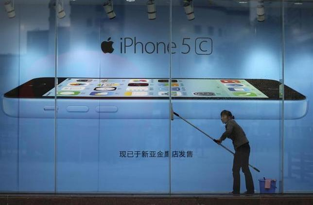 A worker cleans glass in front of an iPhone 5C advertisement at an apple store in Kunming, Yunnan province, in this October 27, 2013 file picture. REUTERS/Wong Campion/Files